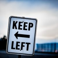 An image of a tilted street sign which reads Keep Left taken at dusk, with a hint of bokeh, by Jon Armstrong.