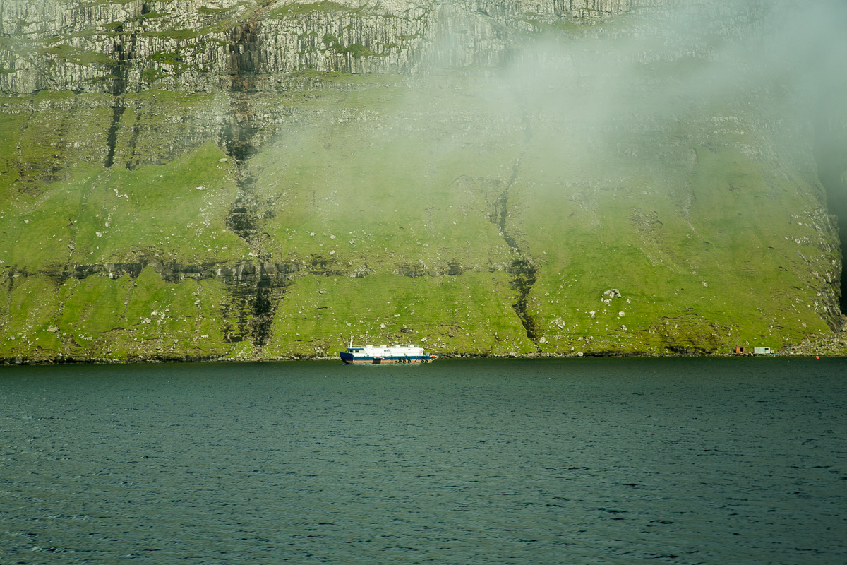 Boat and buildings show the massive height and scale of the Faroe Islands. - Blurbomat.com