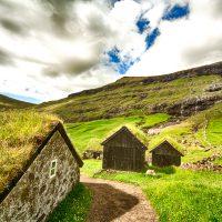 Grass roofed bulidings near a waterfall in Saksun, Faroe Islands | Blurbomat.com