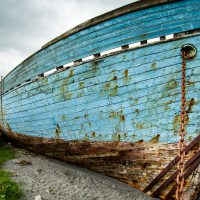 Wide angle photo of a blue wooden boat in Fuglafjørður, Faroe Islands by Jon Armstrong for Blurbomat.com.