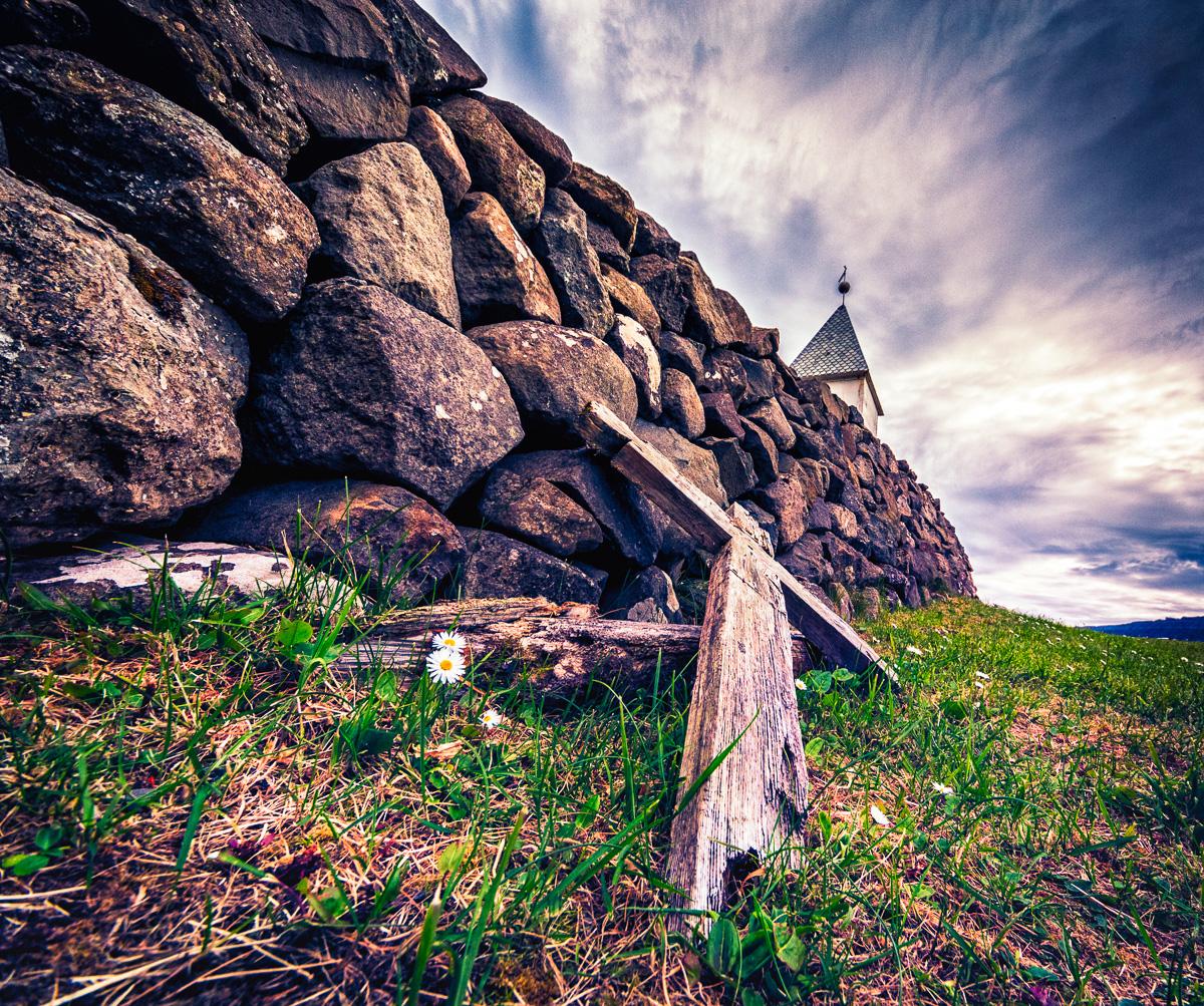 Broken wooden crucifix along the church's rock wall at Vidareidi, Faroe Islands. by Jon Armstrong for Blurbomat.com.