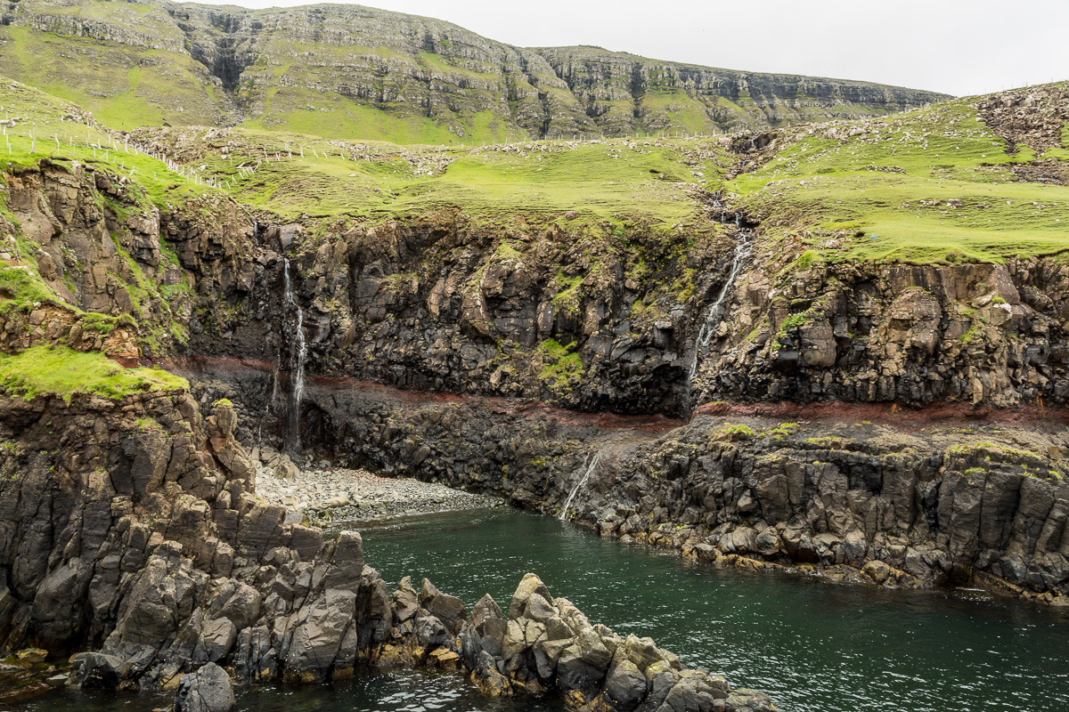 The clay layer erodes more quickly than the stone aboe and below. Suduroy, Faroe Islands.