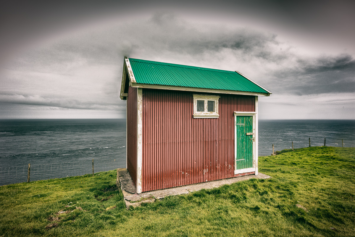 Don't recall if this is an outhouse, shed or storage building. This sits atop the cliff near Akraberg, Suduroy, Faroe Islands.